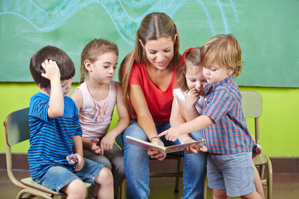 Kinder und Erzieherin lesen Buch im Kindergarten